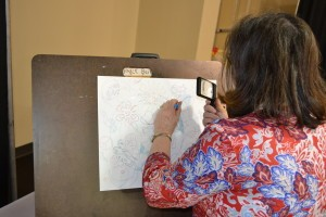 gayle Beireis demonstrates her creative process - pointillism - at the Greene County Council on Aging Expo. She uses micro-pens and a magnifing glass to add detail to her work.