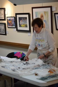 Karen cuts a section of paint covered plastic sheeting to illustrate her creative process.