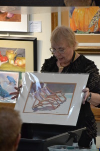 Sandy shows a work that she has completed using the pouring paint technique she demonstrated for the F.A.A. members.